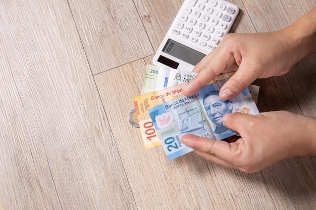 Mani che danno soldi con il calcolatore sulla tavola di legno