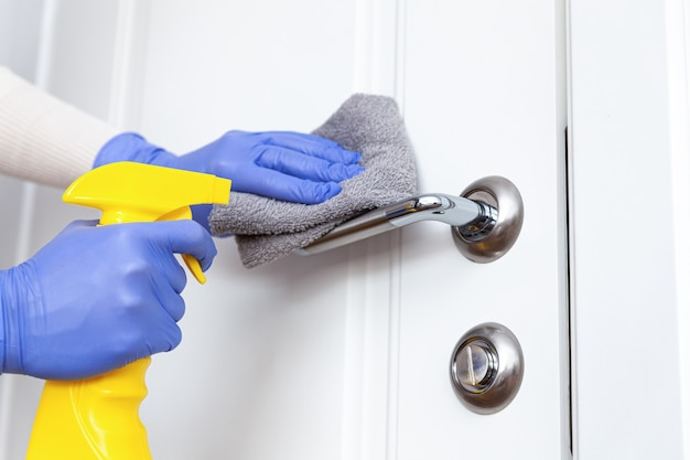 Mani nei guanti che disinfettano la maniglia della porta con uno straccio e un detergente spray