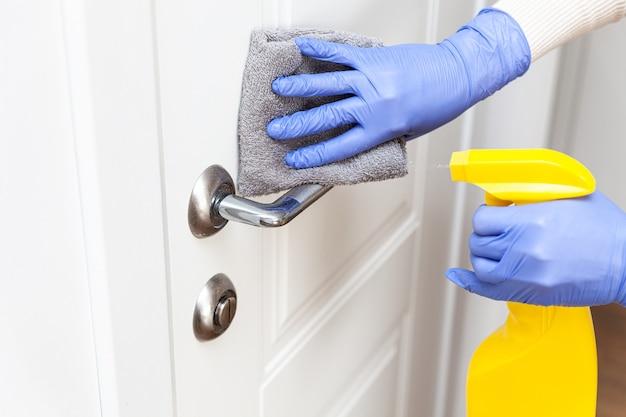 Mani in guanti che disinfettano la maniglia della porta con uno straccio e un detergente spray