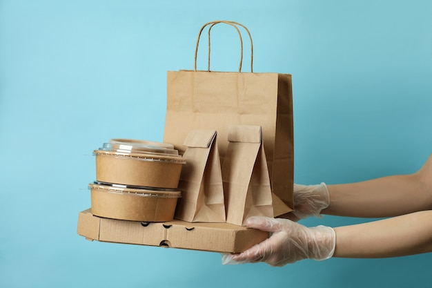 Le mani nei guanti tengono i contenitori di consegna per il cibo da asporto sulla superficie blu