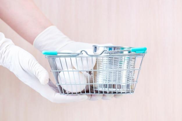 Mani in guanti che tengono un cestino con alimento