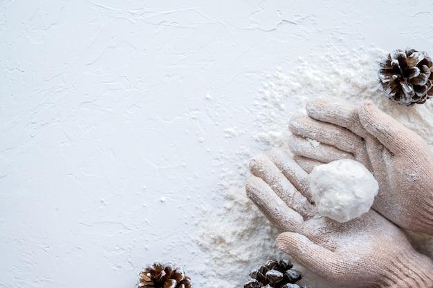 Mani in guanti che tengono una palla di neve, tavolo con neve e pigne. vista dall'alto