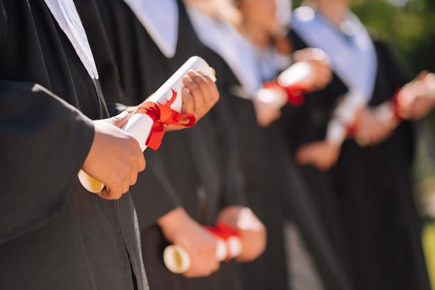 Mani di laureati che tengono i loro diplomi arrotolati con nastri rossi su di loro
