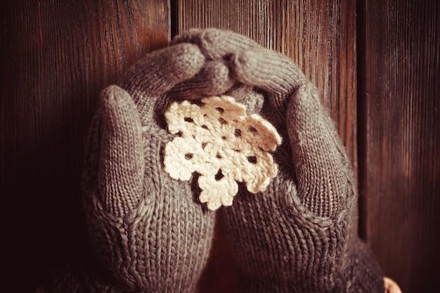 Mani in guanti grigi che tengono un fiocco di neve a maglia bianca su uno sfondo di legno
