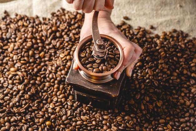 Mani che macinano su una smerigliatrice manuale fragranti chicchi di caffè