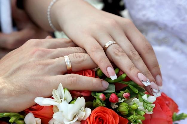 Mani dello sposo e della sposa su sfondo di bouquet da sposa