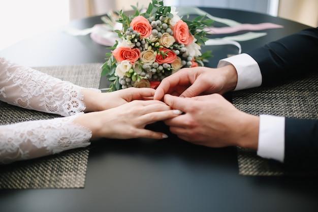 Mani dello sposo e della sposa e un bellissimo bouquet da sposa