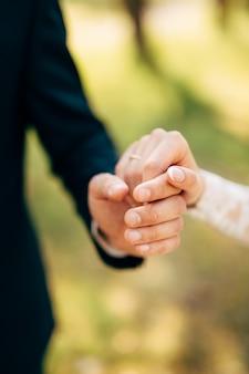 Le mani dello sposo e della sposa tengono insieme.