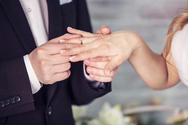 Le mani dello sposo e della sposa indossa un anello al dito il giorno della cerimonia di matrimonio. oro, simbolo, religione, amore.
