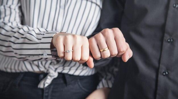 Mani di un ragazzo e una ragazza con la fede nuziale.