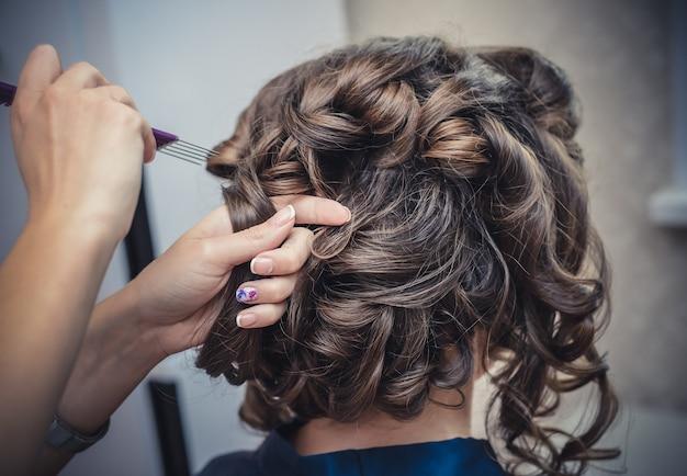 Le mani del parrucchiere fanno acconciatura da sposa con riccioli per primo piano lunghi capelli castani