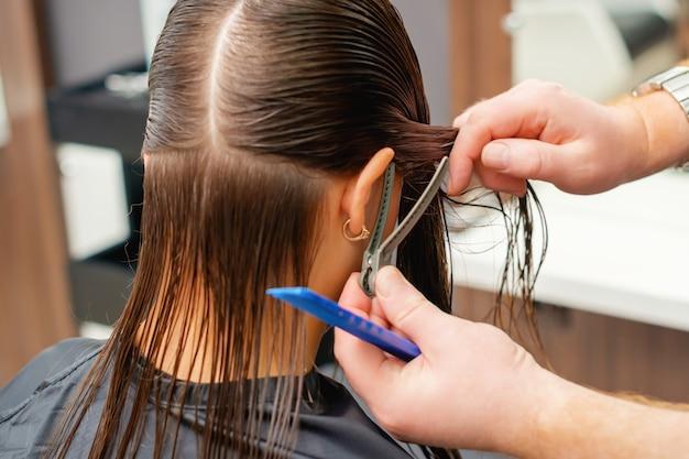 Le mani del parrucchiere pettina i capelli della giovane donna nel parrucchiere