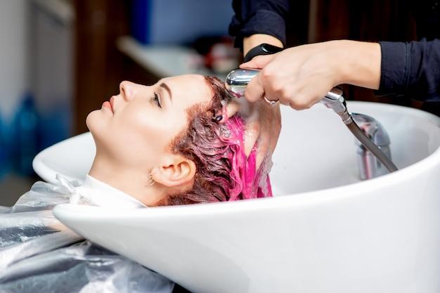 Mani del parrucchiere che lavano i capelli.