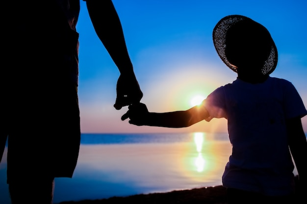 A mani di felice padre e figlio in riva al mare sul viaggio silhouette natura