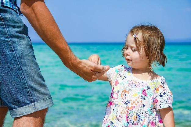 Mani del genitore e del bambino felici al fondo della grecia del mare