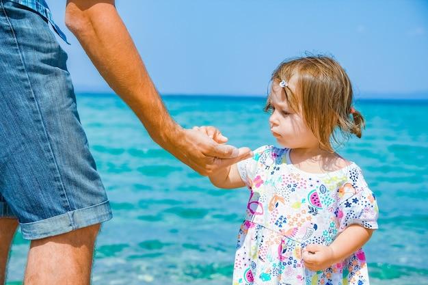 Mani di felice genitore e bambino in mare grecia sfondo