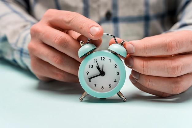 Le mani tengono la sveglia. concetto di trascorrere il tempo utilmente, gestione aziendale