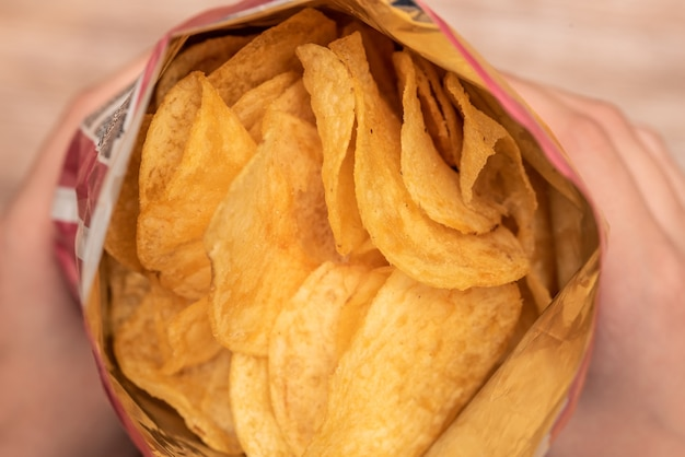 Le mani tengono un sacchetto di patatine fritte. cibo spazzatura a base di colesterolo. salato e croccante. spuntino di fast food. colore giallo.
