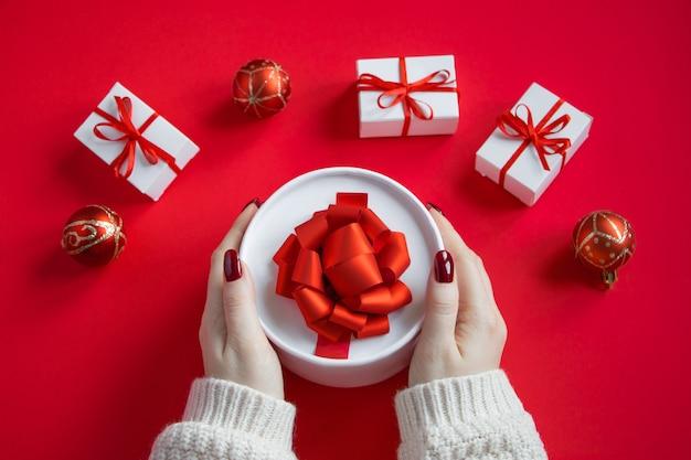 Le mani tengono la bella confezione regalo con fiocco su uno sfondo rosso. concetto di natale.