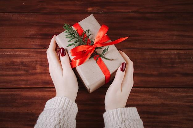 Le mani tengono bella confezione regalo su uno sfondo di legno. tradizione natalizia.