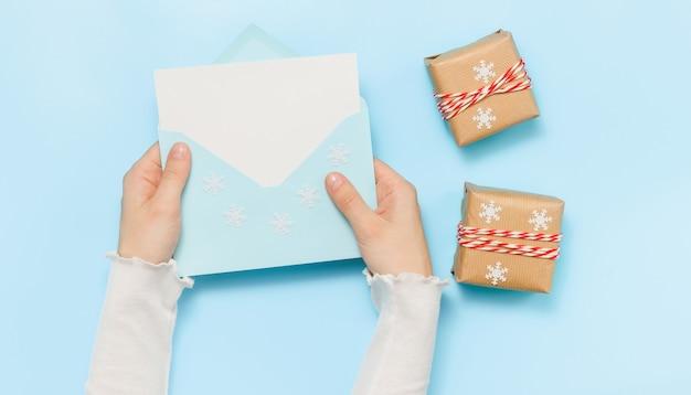 Le mani tengono la busta blu con carta bianca e regali per le vacanze