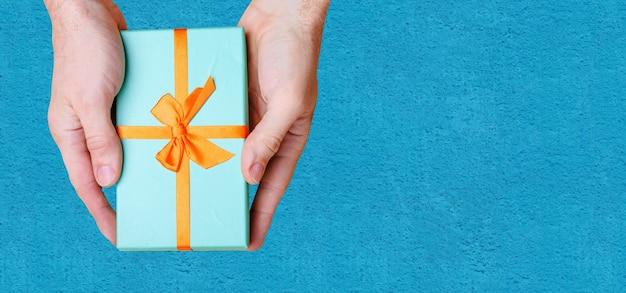Le mani tengono una scatola blu con un fiocco arancione contro il muro blu. vista dall'alto