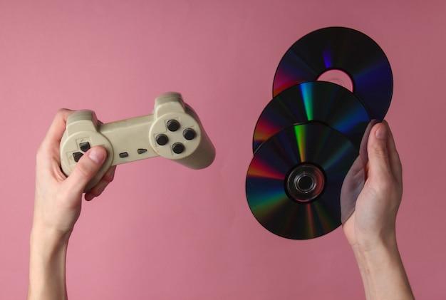 Le mani tengono i dischi cd e il gamepad sulla superficie pastello rosa
