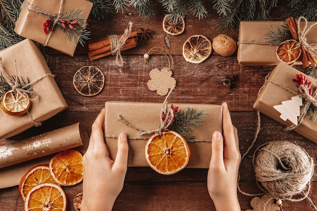 Le mani tengono un regalo di natale avvolto in carta kraft e materiali naturali