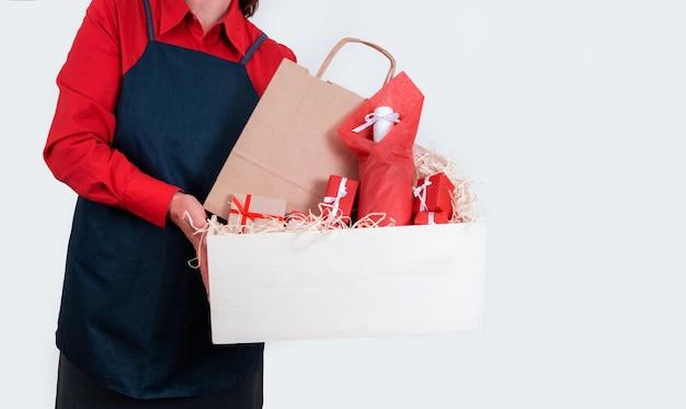Le mani tengono regali, sacchetto di imballaggio e bottiglia di vino