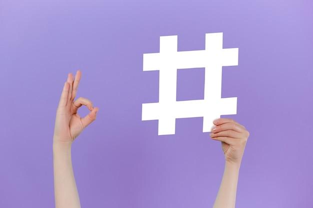 Le mani tengono un grande cartello hashtag e mostrano ok