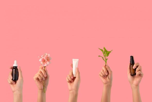 Le mani tengono la cura della pelle cosmetica naturale su sfondo rosa
