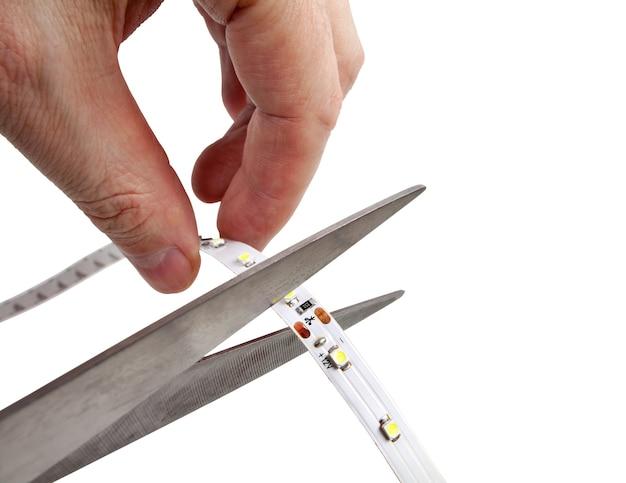 Le mani tengono le forbici che stanno tagliando la striscia led.