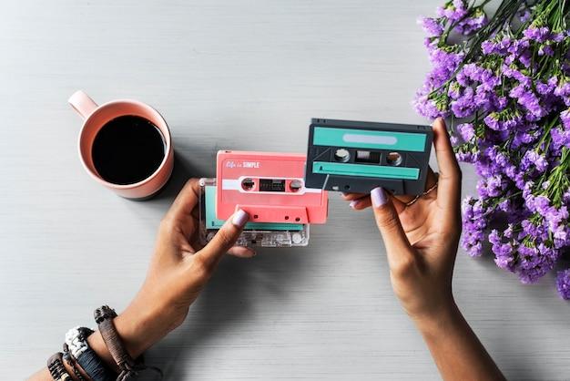 Le mani tengono la rappresentazione del nastro a cassetta audio di musica retro 80s