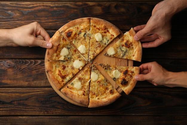 Le mani tengono fette di gustosa pizza al formaggio, vista dall'alto