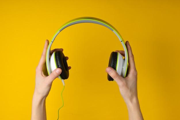 Le mani tengono le cuffie stereo su una superficie gialla