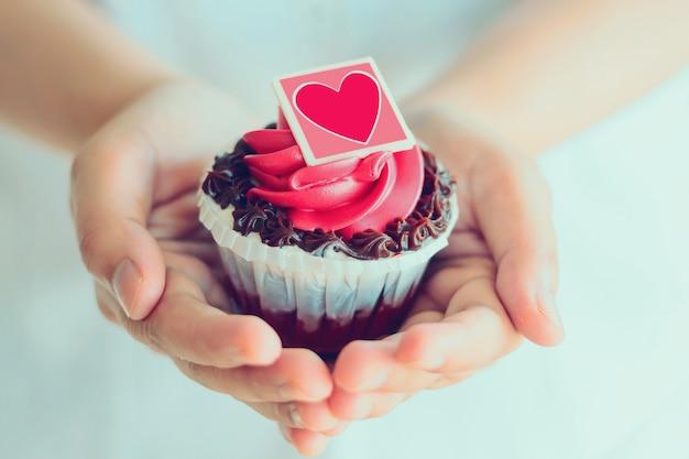 Le mani tengono il cupcake di san valentino
