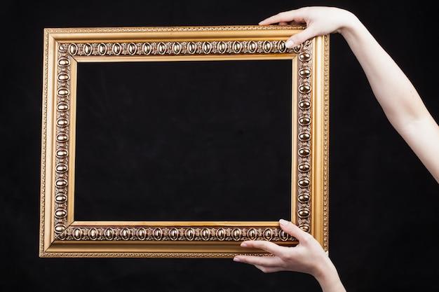 Le mani tengono il telaio vintage su sfondo nero