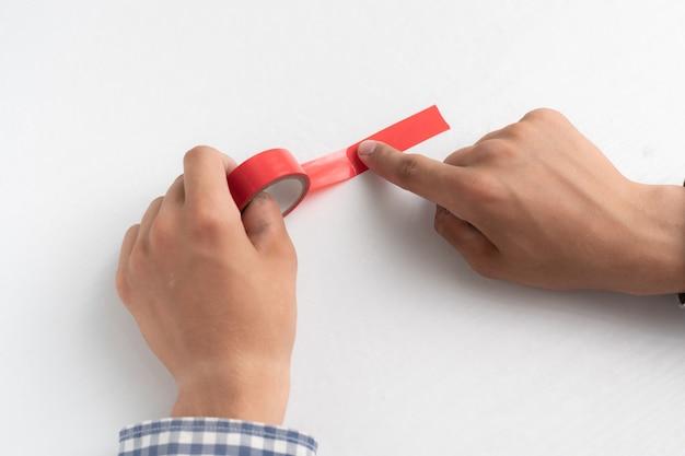 Mani che tengono un nastro adesivo colorato e lo applicano sulla superficie bianca