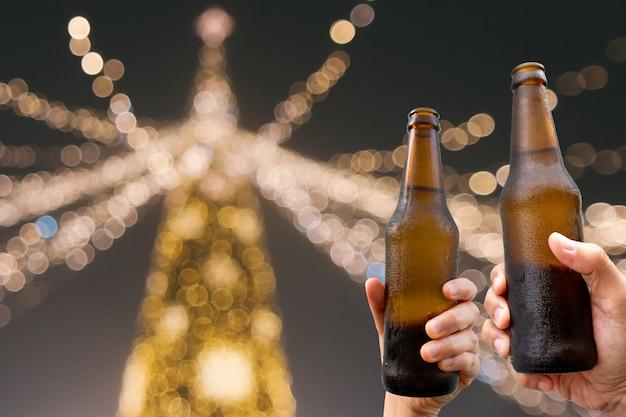 Mani che tengono le bottiglie di birra e tempo di raccolta godendo felice insieme ai vetri tintinnanti alla festa all'aperto