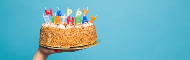 Mani che tengono una torta di compleanno con candele e l'iscrizione compleanno su sfondo blu. congratulazioni per l'anniversario e il compleanno. copyspace