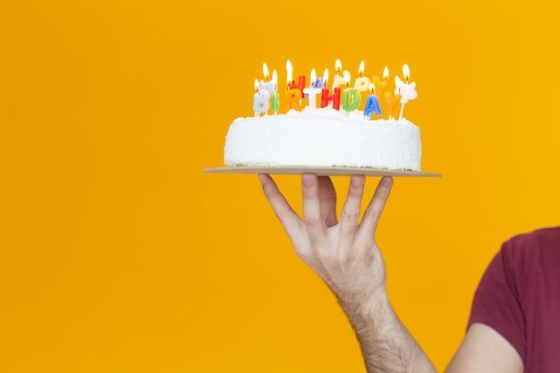 Mani che tengono una torta di compleanno con candele e l'iscrizione compleanno su sfondo giallo