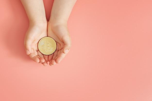 Mani che tengono bitcoin, giornata mondiale del bitcoin, investimento nei bambini futuri, stabilità durante il coronavirus, investimento familiare, responsabilità sociale delle imprese, concetto di investimento Foto Premium