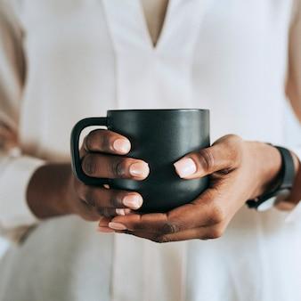 Mani che tengono una tazza di caffè nera