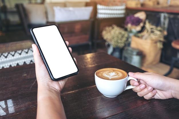 Mani che tengono il telefono cellulare nero con schermo vuoto mentre beve il caffè nella caffetteria vintage