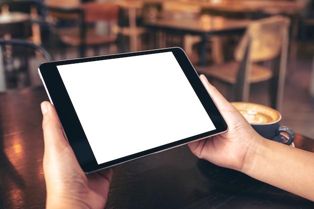 Mani che tengono tablet pc nero con schermo bianco vuoto con tazza di caffè sulla tavola di legno nella caffetteria