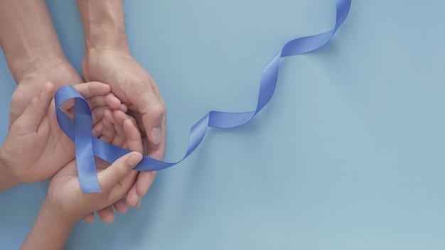 Mani che tengono il nastro blu, consapevolezza del cancro alla prostata, consapevolezza della salute degli uomini