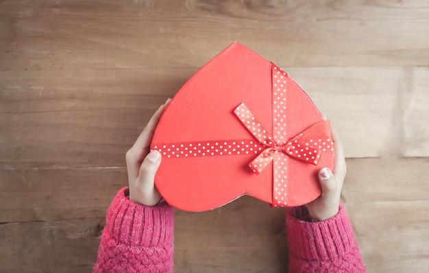 Mani che tengono una scatola a forma di cuore su fondo di legno.