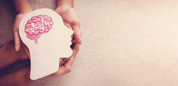 Mani che tengono la carta del cervello, epilessia, consapevolezza di alzheimer, concetto di salute mentale