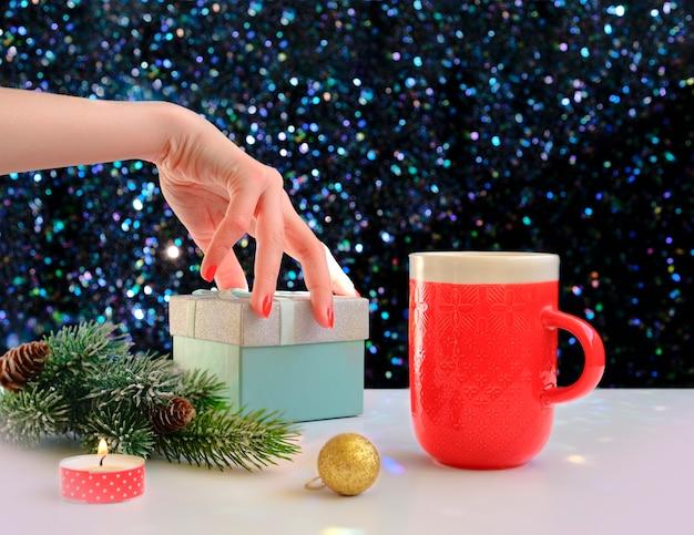 Mani che tengono una tazza di caffè su uno sfondo di natale. vista dall'alto. mani femminili che tengono tazza di caffè. contenitori di regalo di natale e albero di abete della neve sopra il tavolo in legno.
