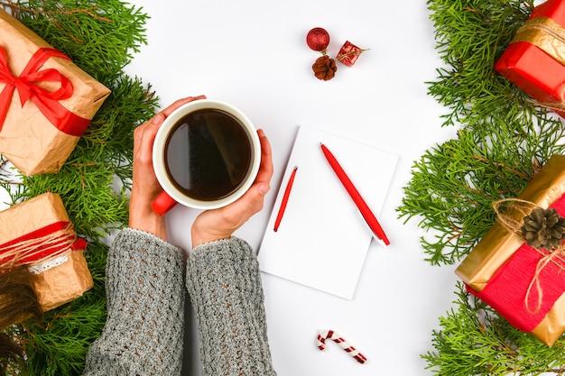 Mani che tengono una tazza di caffè su uno spazio di natale. vista dall'alto. mani femminili che tengono tazza di caffè. contenitori di regalo di natale e albero di abete della neve sopra il tavolo in legno. vista dall'alto con copia spazio.
